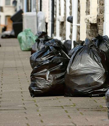 Image of a street with lots of black bin bags awaiting rubbish removal in Cambridge.