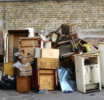 Image of discarded, old, broken pieces of wood, furniture and appliances outside awaiting rubbish removal in Cambridge.
