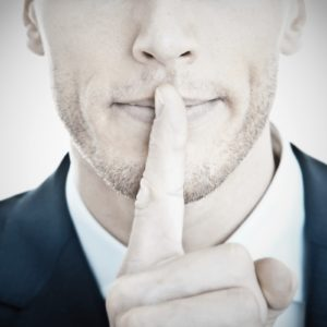 Man with his finger to his mouth to illustrate money-saving moving secrets large Cambridge Removal Companies keep